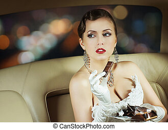 Beautiful and rich superstar girl sitting in a retro car and...