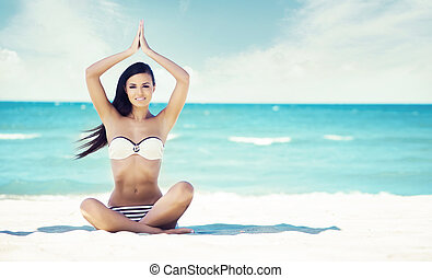Beautiful and sexy young girl meditating on a summer beach....
