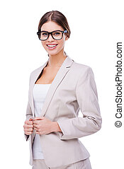 Beautiful and smart. Confident young businesswoman adjusting her jacket and smiling while standing against white background