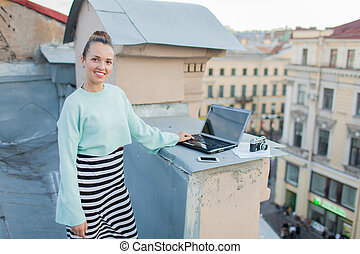 Beautiful and stylish girl works for a laptop on the roof of the house in the old town. on the table are also documents and old camera