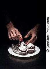 Close up of mans hands decorating cupcakes