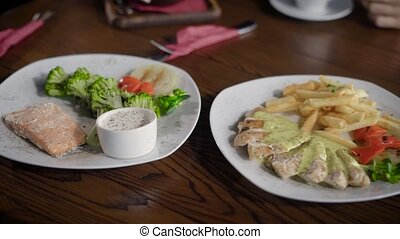 Beautiful and tasty dishes with fish, chicken, salad and sauces. A table in the restaurant is open for two. Meal with tasty and healthy food.