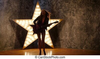 beautiful and young girl with electric guitar, shining star in the background. slow motion, silhouette
