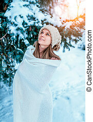Beautiful and young girl wrapped in a white scarf and plaid. Happy looks up on falling snow in winter forest. Against the background of snowy green Christmas trees. Rest during winter day in nature.