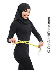 Beautiful arab saudi fitness woman measuring her waist with a tape measure