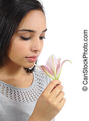 Beautiful arab woman smelling a flower