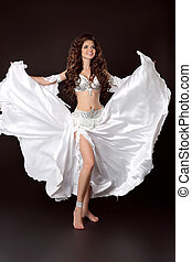 Beautiful Arabian bellydancer sexy woman in bellydance white costume isolated on black background. Sensual arabic girl belly dancer dancing. Belly dance movement in action.