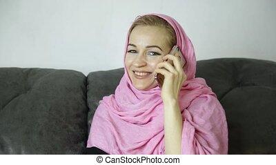 beautiful arabian woman in pink hijab sitting on a sofa in a...