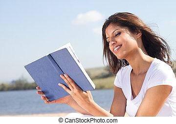 beautiful arabic woman reading book on the beach
