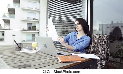 Beautiful architect on balcony working from home. -...