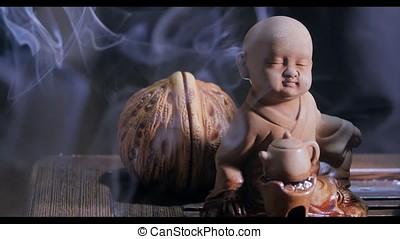 Beautiful aroma smoke near the figurine. uddha Figure On...