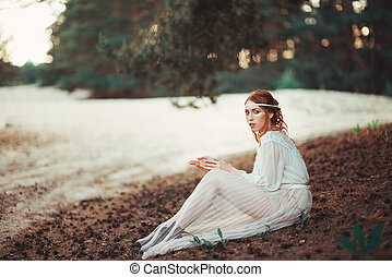 Beautiful artistic photo portrait of a mysterious girl in white dress sitting on the shore of the lake near the forest
