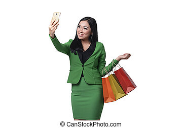 Beautiful asian business woman holding shopping bag and taking selfie