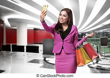 Beautiful asian business woman with shopping bags taking selfie using her smartphone