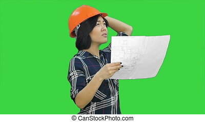 Beautiful asian businesswoman engineer holding the blueprint and wearing the safety helmet on a Green Screen, Chroma Key