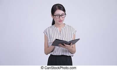 Beautiful Asian businesswoman reading book with eyeglasses