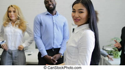 Beautiful Asian Businesswoman Smiles While Business People...