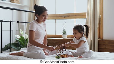 Beautiful asian ethnicity young woman playing toys with small daughter.