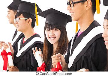 beautiful asian female college graduate at graduation with classmates