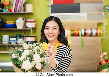 Beautiful asian female florist holding bouquet of flowers