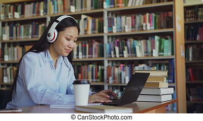 Beautiful asian female student listening music in headphones...