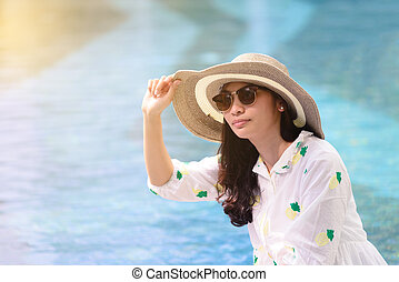 Beautiful Asian girl in sunglasses is relaxing at poolside in summer.