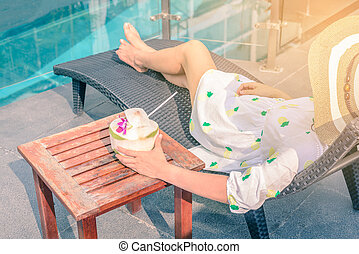 Beautiful Asian girl in sunglasses is sleeping and holding coconut drink at poolside in summer.