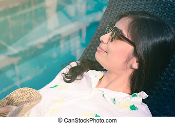 Beautiful Asian girl in sunglasses is sleeping at poolside in summer.