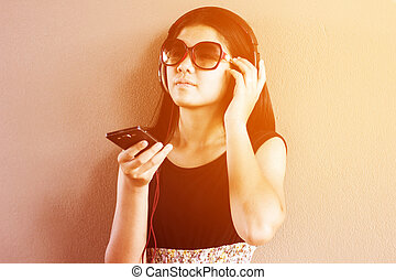 Beautiful asian girl listening to music from smart phone