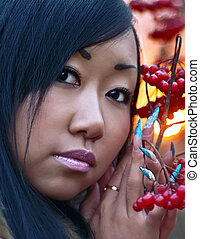 Beautiful asian girl with berry in hand
