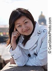 Beautiful asian girl posing outdoors in city