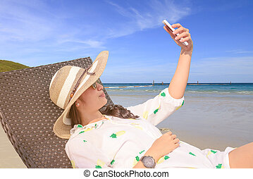 Beautiful Asian girl selfie with smartphone on bench near beach in summer.