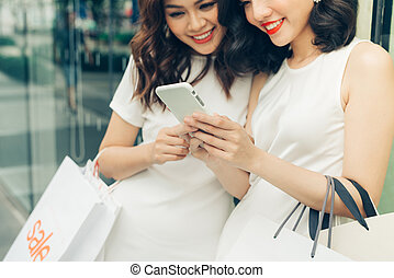 Beautiful asian girls with shopping bags using smartphone at the mall
