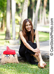 Beautiful Asian lady in black dress, posing in the park,...