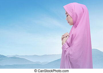Beautiful asian muslim woman wearing hijab praying