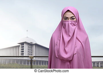 Beautiful asian muslim woman with niqab standing against...