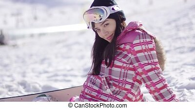 Beautiful asian snowboarder sitting on snow