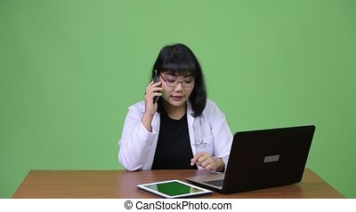 Beautiful Asian woman doctor multi-tasking and calling at work