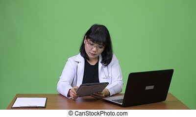Beautiful Asian woman doctor multi-tasking at work