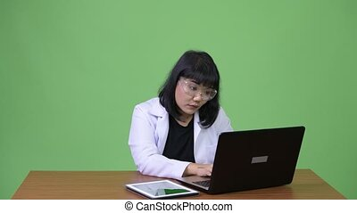 Beautiful Asian woman doctor wearing protective glasses multi-tasking at work