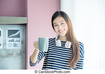 Beautiful asian woman drinking coffee in office and smile