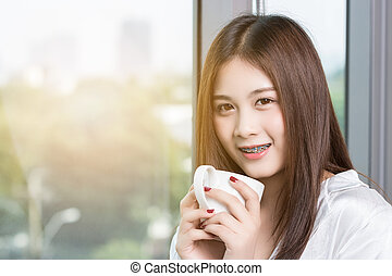 Beautiful Asian woman drinking coffee in the morning happily.