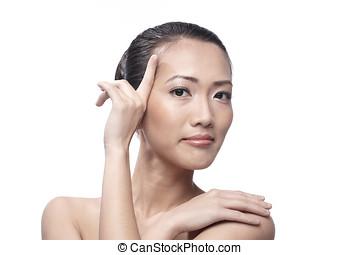Beautiful Asian woman gently touching her face.