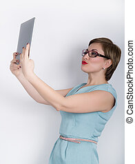 beautiful asian woman in a business suit and glasses holds a tablet in the hands of