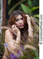 Beautiful Asian woman in lingerie posing outdoors.