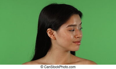 Beautiful Asian woman looking to the sides, then smiling to...