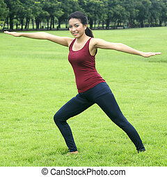 beautiful Asian woman practicing yoga nature