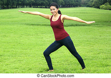 beautiful Asian woman practicing yoga nature in the park