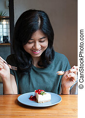 Beautiful asian woman prepare to eating a cake in cafe