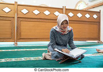 beautiful asian woman read quran in the mosque